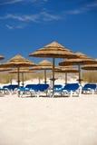 Strohregenschirme mit Strandstühlen Lizenzfreies Stockfoto