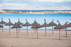 Strohregenschirme und leerer Strand Stockbilder