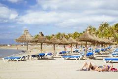 Strohregenschirme und -ruhesessel auf dem Playa De Las Amerika, Tener Lizenzfreie Stockfotos
