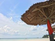 Strohsonnenschirm mit dem roten Kleid, das an einem schönen Strand hängt Lizenzfreies Stockfoto