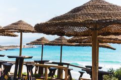 Strohsonnenschirme durch das Meer Lizenzfreie Stockfotografie