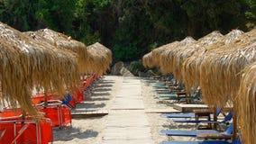 Strohsonnenschirme (Regenschirme) auf einem sandigen Strand. Lizenzfreie Stockfotografie