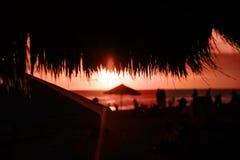 Strohstranddach im Caf? mit unscharfen Leuten auf korallenrotem Sonnenuntergang stockfotografie
