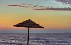 Strohstrandschirm auf einem Hintergrund des Meeres und der Abendhimmel auf der Insel von Korfu Lizenzfreies Stockbild