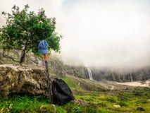 Stroju wycieczkowicz Plecaki, chodzący kije i turysty nakrętka w górach na postoju pod drzewem, obraz royalty free