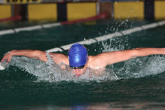 Stroke. Butterfly stroke by male swimmer with blue cap Stock Photos