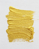 Strokes of gold acrylic paint isolated on white Royalty Free Stock Images