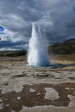 Strokkur geyser erupting. Icelands famous geyser Strokkur erupts. Nice shot at a sunny day against a cloudy sky Stock Photos