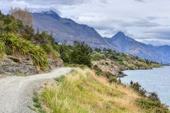 A stroll along Lake Wakatipu in New Zealand makes for a great afternoon. Trails align the shoreline of Lake Wakatipu in Queenstown, New Zealand, which offers royalty free stock photo