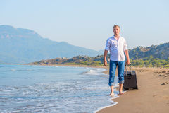 Stroll along the sandy beach. With luggage Royalty Free Stock Image
