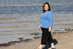 Stroll on the Beach. Beautiful plus sized model taking a relaxed stroll on the beach stock photo