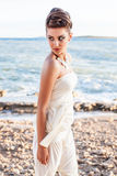 Stroll on the beach. A beautiful brunette model wearing a cream silk one piece looking back over her bare shoulder while strolling along the beach royalty free stock photo