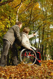 Stroll in the fall park. Husband and handicapped wife taking stroll in park alley in fall time royalty free stock photography