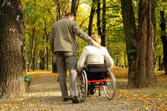 Stroll in the fall park. Husband and handicapped wife taking stroll in park alley in fall time royalty free stock image