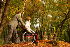 Stroll in the fall park. Husband and handicapped wife taking stroll in park alley in fall time stock image