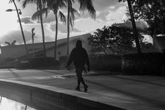 On a stroll in the park. Hollywood Florida Young circle park showing a hooded man walking down the sidewalk with the mist from the sprinklers in the sunny air stock image