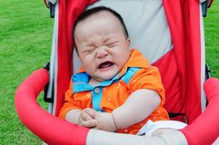 The stroller crying baby. A Chinese children crying in the park Royalty Free Stock Photo