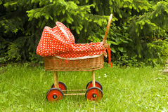 Stroller, pram, red baby buggy. Red baby stroller or pram in green grass and tree background, colour contrast concept Royalty Free Stock Photography