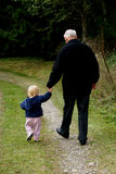 The strollers hand-in-hand. Grandpa and toddler grandchild holding hands strolling down country lane Stock Photo