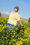 Strolling by. Happy older woman walking in a vibrant meadow Royalty Free Stock Photography