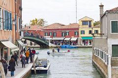 Strolling along canal in Murano. Venice, Italy, Oct 24 2011: Tourists and shoppers strolling along a canal in Murano, Venice, Italy Royalty Free Stock Photos