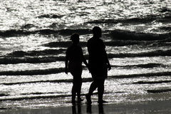 Strolling on the Beach. Old couple taking a sunset stroll on the beach Stock Photos