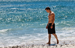 Strolling the Beach. A thoughtful young man walks along the edge of blue ocean water on white sand littered with rocks Stock Image