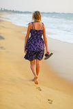 Strolling the beach. Beautiful young blond girl taking a stroll on the beach with flipflops in hand Royalty Free Stock Photography