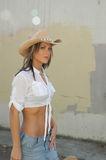 Strolling Cowgirl. Beautiful blond cowgirl strolling. Cowboy hat, white half-top, and blue denim skirt stock photos