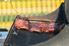 Strom der Barbecue-Soße beschichtet die Rippen, die auf Grill kochen Stockfoto