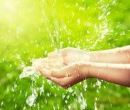 Strom des Trinkwassers gießend in die Hände des Kindes Stockbilder