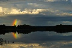 Strom Rising. Over calm lake with gorgeous short rainbow Stock Images