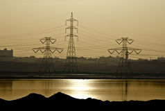 Strom-Verteilungs-Kontrolltürme am Sonnenuntergang Stockbild
