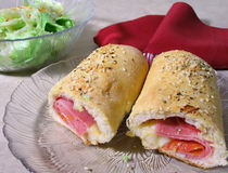 Stromboli. Italian sandwich with meat and cheese rolled in bread dough and baked stock image