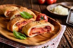 Stromboli ha farcito con formaggio, salame, la cipolla verde e la salsa al pomodoro Immagini Stock