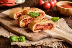 Stromboli met kaas, salami, groene ui en tomatensaus wordt gevuld die stock afbeelding