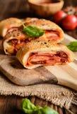 Stromboli rellenó con queso, salami, la cebolla verde y la salsa de tomate Imagen de archivo