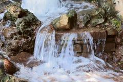 Stromen die van water onderaan de stenen stromen Stormachtige stromen van water royalty-vrije stock fotografie