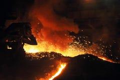 Stromen van gesmolten ijzer in een hoogoven met vonken Stock Afbeelding