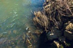 Stromend water in de rivier met rotsachtige bank in de vroege lente stock afbeeldingen