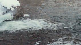 Stromend water Gouden rimpelingen in water De winterrivier Snel rivierwater Steen met ijs stock footage