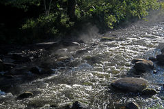 Stromend water over rotsen en keien stock foto's
