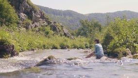 Stromend water van bergrivera en vrouwenzitting op de steenachtige mening van de kust lage hoek stock video