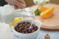 Stromende melk op de ballen van de graangewassenchocolade, chocoladevlokken royalty-vrije stock afbeelding