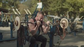 Stromg bodybuilder performing barbell biceps curls. Handsome concentrated strong fit man performing barbell biceps curls while sitting on bench in outdoor gym stock video