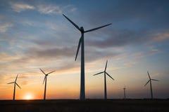 Stromgeneratoren von Windmühlen bei Sonnenuntergang des Tages Lizenzfreies Stockbild