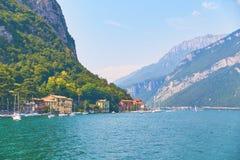 Stromi wysokogórscy banki piękny jeziorny Como z parkującymi jachtami i łodziami zbliżają wioskę Pare, Włochy fotografia stock