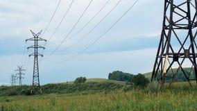 Stromleitung ragt, verrostete Metallstrahlen, Sommervegetation und drastischer stürmischer Himmel, Wolken im Hintergrund hoch Stockfoto