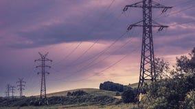 Stromleitung ragt, verrostete Metallstrahlen, Sommervegetation und drastischer stürmischer Himmel, Wolken im Hintergrund hoch Stockfotografie
