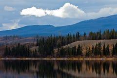 Stromleitung in ruhigem Yukon See im späten Fall, Kanada Lizenzfreie Stockbilder